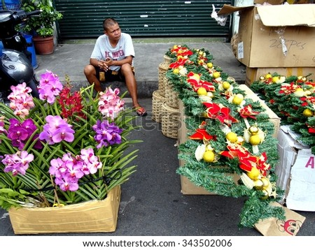 QUEZON CITY, PHILIPPINES - NOVEMBER 22, 2015: A man sells decorative plants and flowers and christmas decors in Dapitan Market. Dapitan Market is known for its wide variety of home decor products. - stock photo