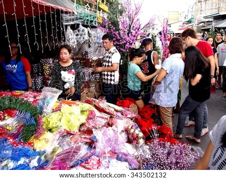 QUEZON CITY, PHILIPPINES - NOVEMBER 22, 2015: Customers look at a wide variety of chirstmas decors at a store in Dapitan Market. Dapitan Market is known for its wide variety of home decor products. - stock photo