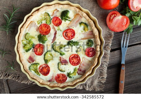 Quiche lorraine traditional french homemade tart pie with bacon tomatoes cheese and broccoli in baking dish on vintage wooden table background. Top shot. Rustic style, natural light. - stock photo