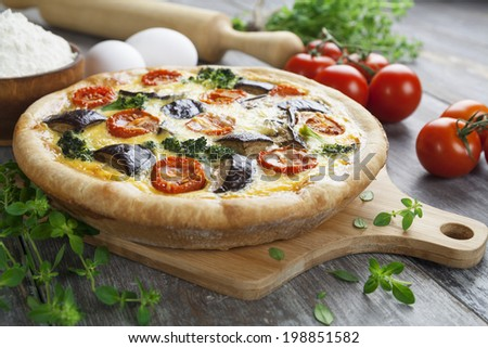 Quiche with cherry tomatoes, broccoli and eggplant on the table