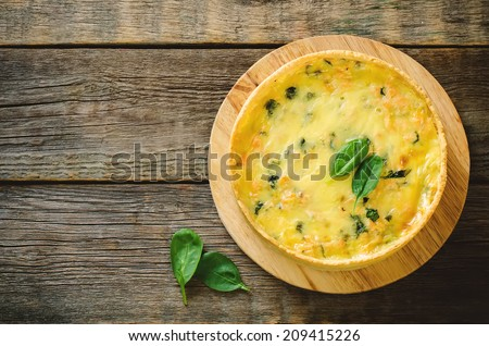 quiche with salmon and spinach on a dark wood background. toning. selective focus on the spinach leaves on the cake - stock photo