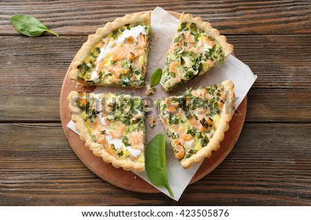 quiche with trout and spinach on wooden boards - stock photo