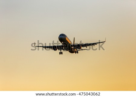 Quick civilian passenger plane in the sky landing to touch the ground. Airplane in the rays of the setting sun in landing mode in airport