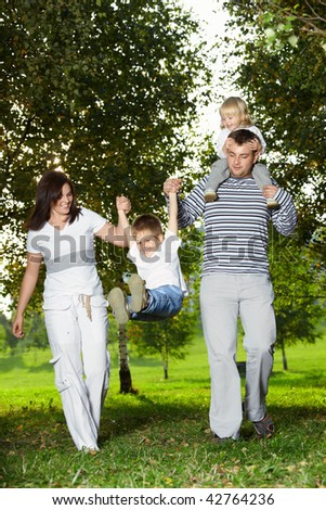 Quick family with small children runs on a lawn - stock photo