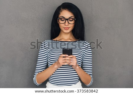 Quick message to friend. Attractive young African woman holding smart phone and looking at it while standing against grey background - stock photo