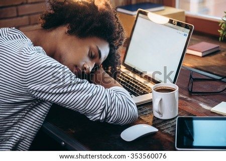 Quick nap. Side view of young African man sleeping on laptop with eyes closed while sitting at his working place - stock photo