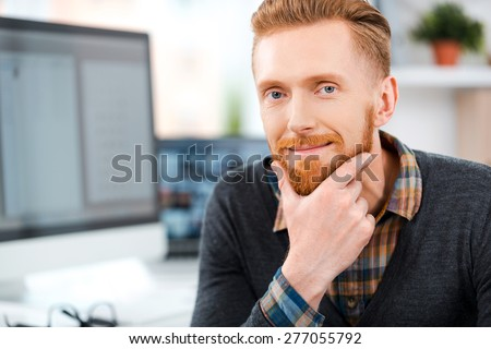 Quiet confidence. Smiling young bearded man looking at camera and holding hand on chin while sitting at his working place - stock photo