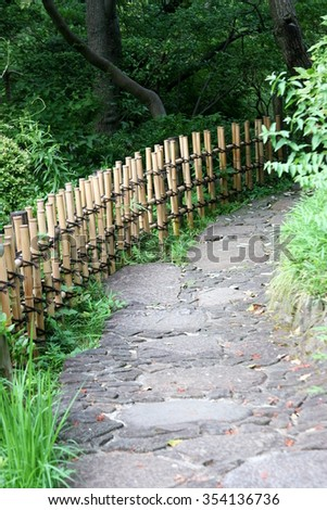 Quiet Japanese garden footpath in the lush of greens - stock photo
