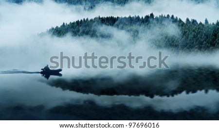 Quiet mountain lake in a thick fog. In the background a mountain forest. Floats on the water in the boat people. The blue tone. - stock photo