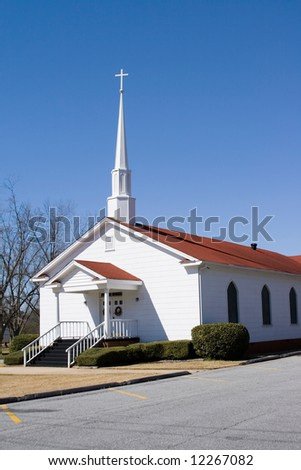 Quiet rural small church with cross and steeple - stock photo