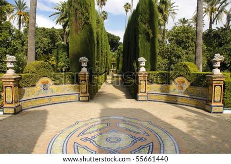 Quiet square with decorated floor and narrow walkway in the gardens of the Royal Alcazar in Seville - stock photo