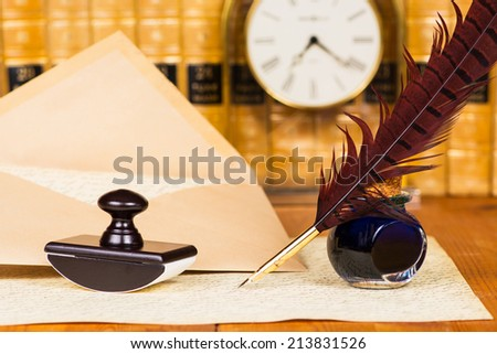 Quill and ink with antique books in the background - stock photo