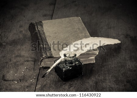 Quill and inkwell, book on old table background - stock photo