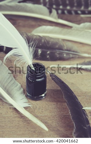 quill in the inkwell with feather - stock photo