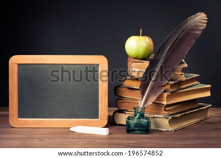 Quill ink pen, old books, chalk board on desk for vintage background - stock photo
