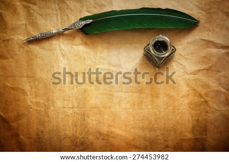 Quill pen and ink well resting on blank parchment paper with copy space for message - stock photo