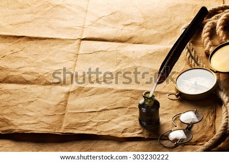 quill pen, inkwell, compass and rope on vintage paper background - stock photo