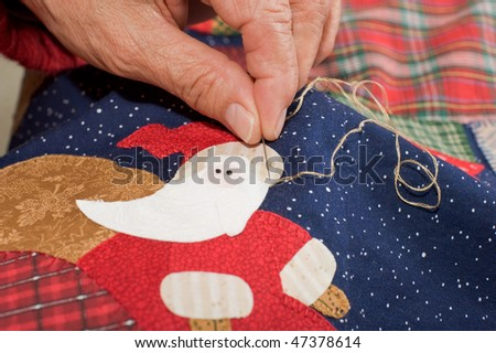 Quilter embroidering santa's brim in place - stock photo