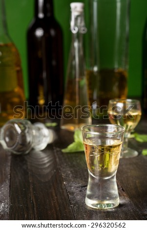 Quince liqueur in glass on wooden table - stock photo
