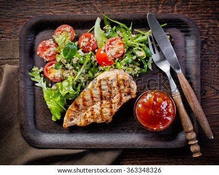 Quinoa and vegetable salad and grilled chicken fillet on dark wooden plate, top view - stock photo