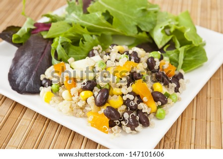 Quinoa and vegetable salada with black beans on a white plate