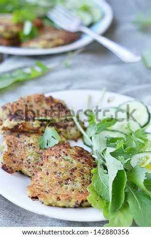 quinoa and zucchini  pancakes with green salad - stock photo