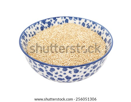 Quinoa in a blue and white porcelain bowl with a floral design, isolated on a white background - stock photo