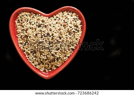 quinoa in a Red heart shaped bowl and wooden table