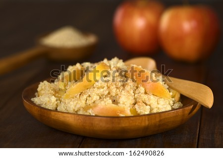 Quinoa porridge with apple and cinnamon, which is a traditional Peruvian breakfast, served on wooden plate (Selective Focus, Focus one third into the porridge) - stock photo