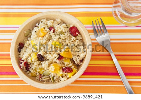 Quinoa salad with dried fruit and colored peppers on a bright summer table cloth