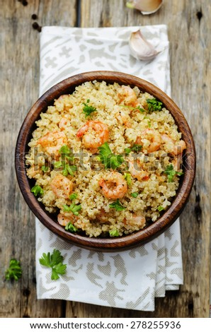 quinoa with shrimp and parsley on a dark wood background. the toning. selective focus - stock photo