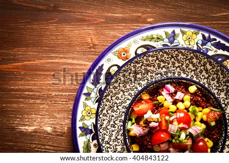 Quinoa with tomatoes chilli and corn on a plate with  black background pattern wood. Flat Lay. Top view. - stock photo