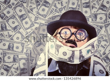 Quirky vintage portrait of a funny business man covered in US Dollars. Drowning in debt concept