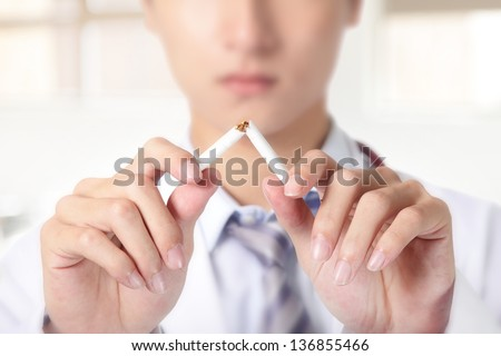 Quit smoking, doctor hands breaking the cigarette, close up, asian model - stock photo
