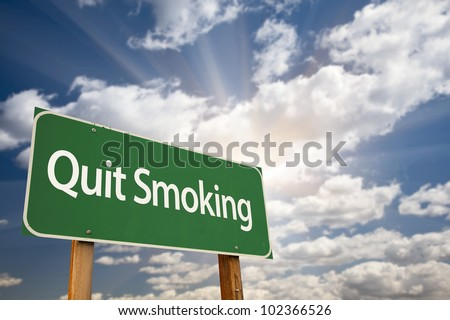 Quit Smoking Green Road Sign with Dramatic Clouds, Sun Rays and Sky.