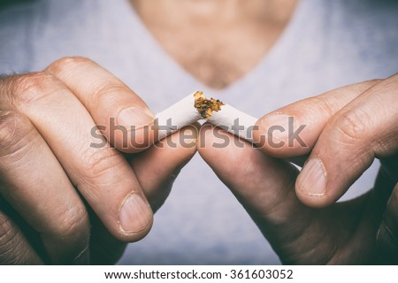 Quit smoking - male hand crushing cigarette - stock photo