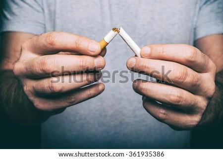 Quit smoking - male hand crushing cigarette - stock photo