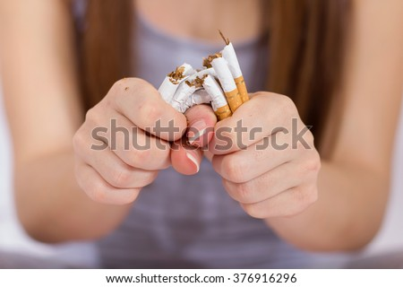 Quit Smoking, woman hands breaking bunch of cigarette. - stock photo