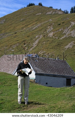 quite confused looking girl stands in the middle of the mountains and tries to find her way on a crumbled map - stock photo