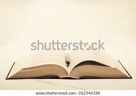 quite old but not damaged open book lying on the table with metal ballpoint pen and paper sheet on a light background - stock photo