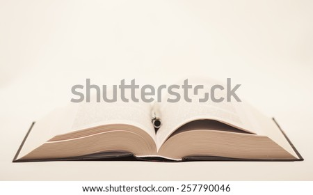 quite old but not damaged open book lying on the table with metal ballpoint pen on a light background - stock photo