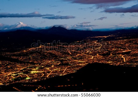 Quito at night with cotopaxi mountain - stock photo