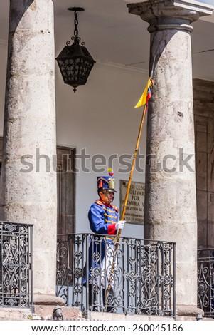 QUITO, ECUADOR - JAN 5, 2015: Unidentified Ecuadorian hussar with the national flag of Ecuador in Quito. 71,9% of Ecuadorian people belong to the Mestizo ethnic group - stock photo