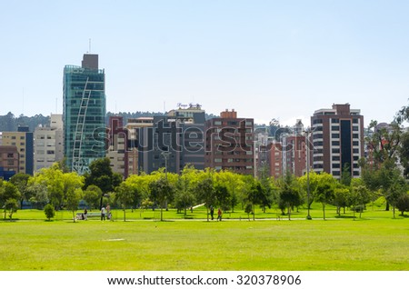 QUITO, ECUADOR- MARCH 20, 2015: Inside La Carolina park in Quito, Ecuador. Beautiful green outdoors with some tall office buildings marking the city presence.