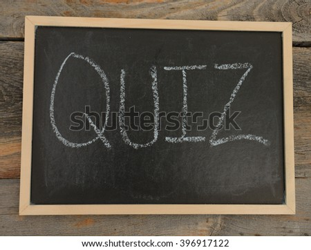 quiz written in chalk on a chalkboard on a rustic background - stock photo