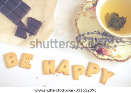 Quote BE HAPPY. Still life image with biscuits, organic chocolate and vintage cup of green tea white wooden background. Top view collage made of biscuits. Retro toned and instagram filtered image.