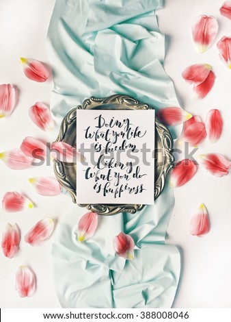 "quote ""Doing what you like is freedom, liking what you do is happiness"" written in calligraphy style on paper with red petals and blue ribbon. Flat lay, top view - stock photo"
