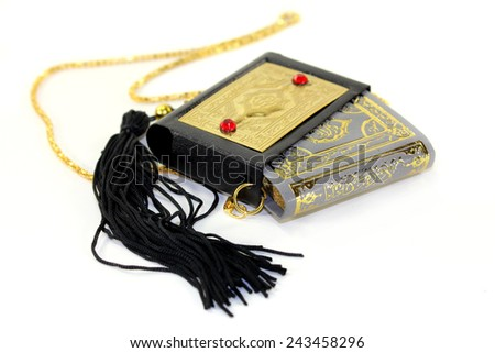 Quran with a cover and chain in front of white background - stock photo