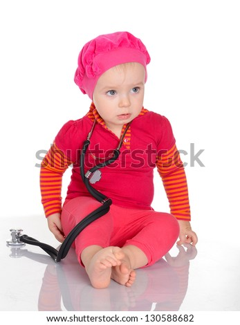 Qute baby girl with phonendoscope sitting on a white background