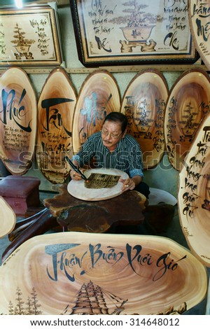 QUY NHON, VIET NAM- AUG 23: Vietnamese artist doing wood engraving by fire pen, man engrave Han Mac Tu poem at souveir shop of Genh Rang tourist area, a famous poet, Quynhon, Vietnam, Aug 23, 2015